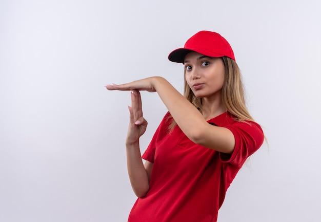 Jong leveringsmeisje die rood uniform en pet dragen die time-outgebaar tonen dat op witte muur wordt geïsoleerd