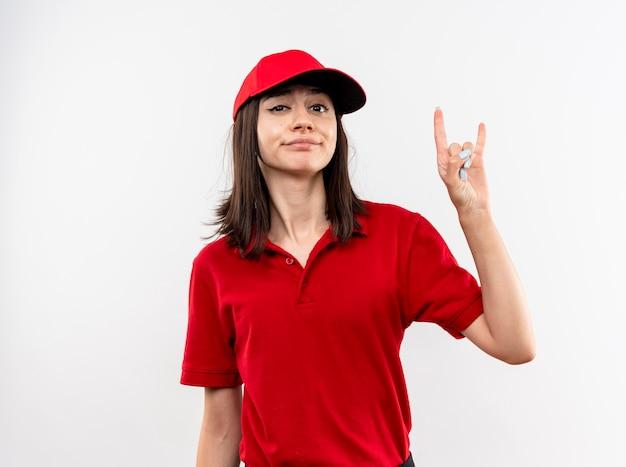 Jong leveringsmeisje die rood uniform en pet met sceptische glimlach dragen die rotssymbool tonen die zich over witte muur bevinden