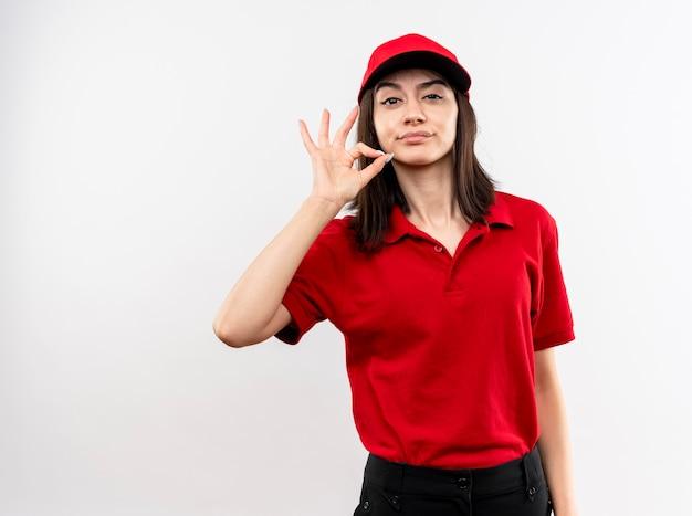 Jong leveringsmeisje die rood uniform en pet met sceptische glimlach dragen die stiltegebaar tonen zoals het sluiten van mond met een ritssluiting die zich over witte muur bevindt