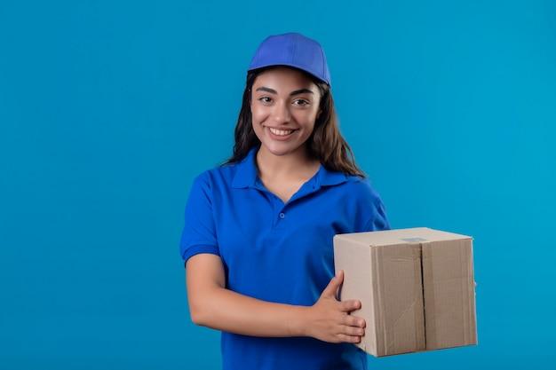 Jong leveringsmeisje in blauw uniform en de doospakket van de glbholding die camera glimlachen die vriendschappelijk status over blauwe achtergrond bekijken