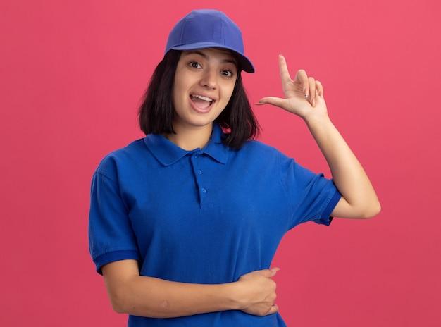 Jong leveringsmeisje in blauw uniform en glb blij en verrast tonende wijsvinger met nieuw idee dat zich over roze muur bevindt