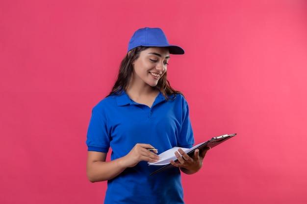 Jong leveringsmeisje in blauw uniform en glb dat klembord met pen bekijkt die het glimlachend zelfverzekerd over roze achtergrond bekijkt