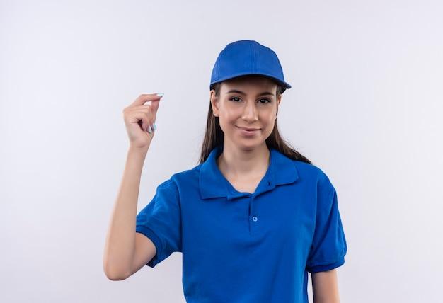 Jong leveringsmeisje in blauw uniform en glb die geldgebaar maken die vingers met glimlach op gezicht wrijven