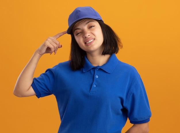 Jong leveringsmeisje in blauw uniform en glb die het krabben hoofd met vinger worden verward die zich over oranje muur bevinden