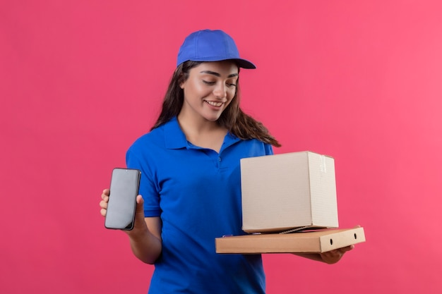 Jong leveringsmeisje in blauw uniform en glb die kartondozen houden die smartphone glimlachend vriendschappelijk status over roze achtergrond tonen