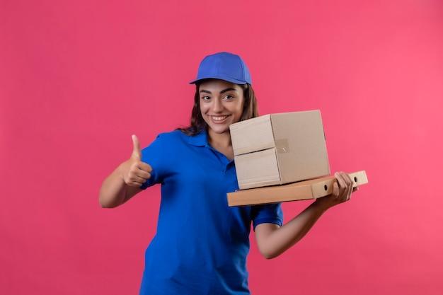 Jong leveringsmeisje in blauw uniform en glb die kartondozen houden die vrolijk glimlachend duimen tonen die zich over roze achtergrond bevinden