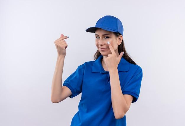 Jong leveringsmeisje in blauw uniform en glb die vingers wrijven die met vinger naar haar oog wijzen die op betaling wachten