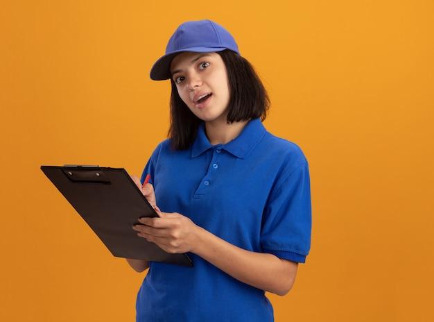 Jong leveringsmeisje in blauw uniform en glb-holdingsklembord die iets schrijven dat zich over oranje muur bevindt glimlachend