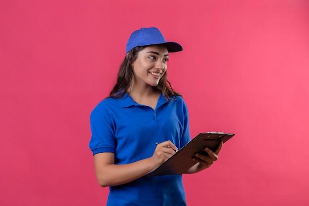 Jong leveringsmeisje in blauw uniform en glb-holdingsklembord met pen die opzij glimlachend zekere status over roze achtergrond kijken