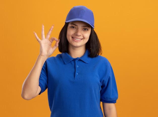 Jong leveringsmeisje in blauw uniform en glb-sniling tonend ok teken dat zich over oranje muur bevindt