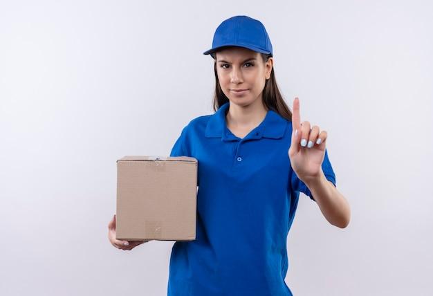 Jong leveringsmeisje in blauw uniform en het pakket dat van de glb-holdingsdoos wijsvingerwaarschuwing met fronsend gezicht toont