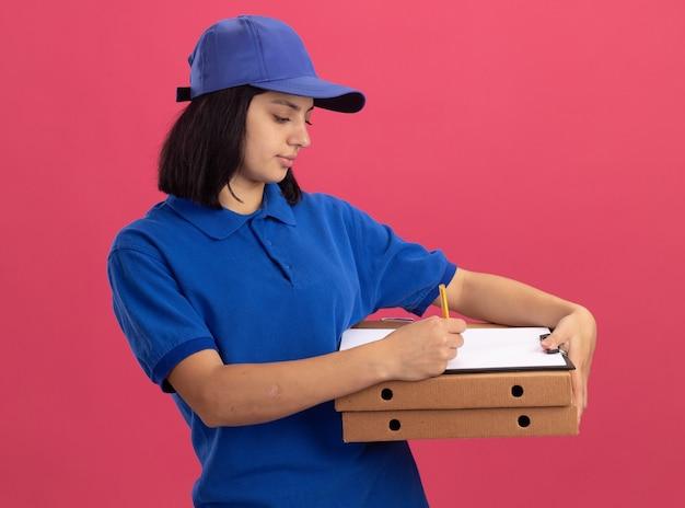 Jong leveringsmeisje in blauw uniform en pet die pizzadozen en klembord houden die iets met ernstig gezicht schrijven dat zich over roze muur bevindt