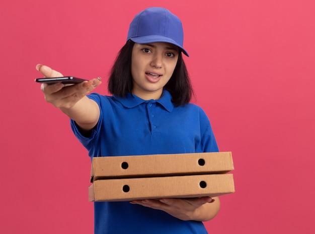 Jong leveringsmeisje in blauw uniform en pet die pizzadozen houden die zich uit mobiele telefoon uitstrekken die zich over roze muur bevindt