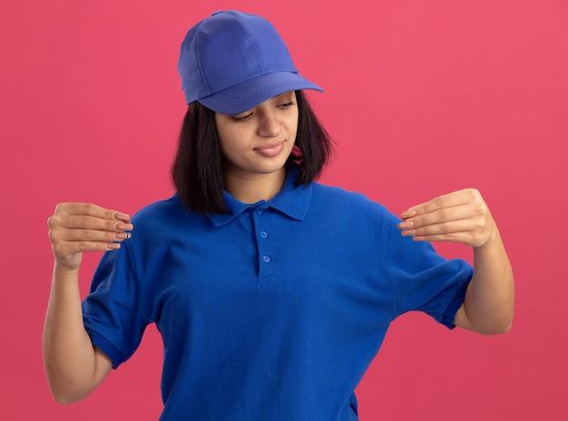 Jong leveringsmeisje in blauw uniform en pet op zoek zelfverzekerd gebaren met vingers, lichaamstaal concept staande over roze muur