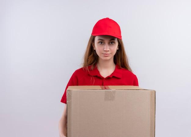 Jong leveringsmeisje in rode eenvormige holdingsdoos en op geïsoleerde witte muur met exemplaarruimte