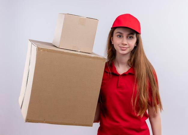 Jong leveringsmeisje in rode eenvormige holdingsdozen op geïsoleerde witte muur