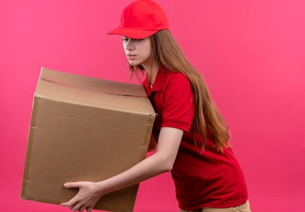 Jong leveringsmeisje in rode uniforme holdingsdoos die naar beneden en status in profielmening op geïsoleerde roze muur kijken