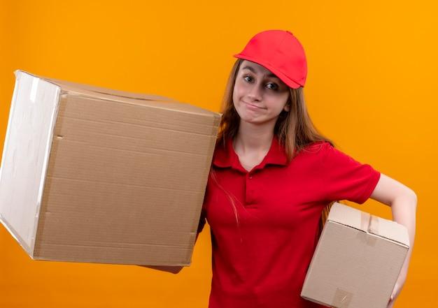 Jong leveringsmeisje in rode uniforme holdingsdozen op geïsoleerde oranje muur