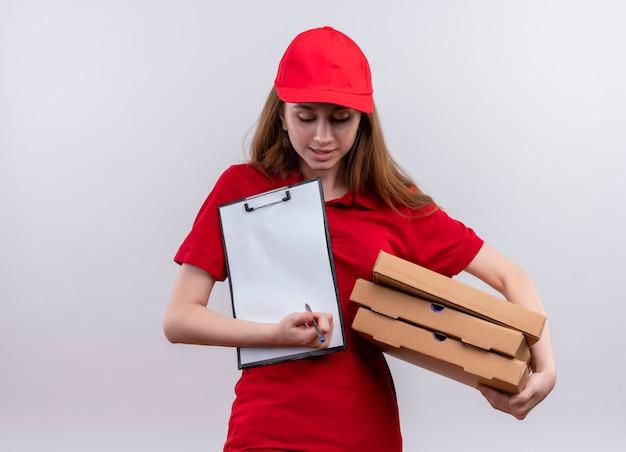 Jong leveringsmeisje in rode uniforme holdingspakketten en pen, klembord die op geïsoleerde witte muur met exemplaarruimte neerkijken