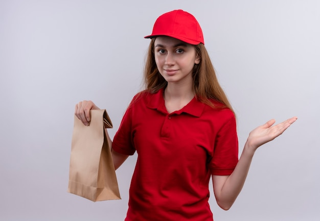 Jong leveringsmeisje in rode uniforme papieren zak houden en lege hand tonen op geïsoleerde witte muur