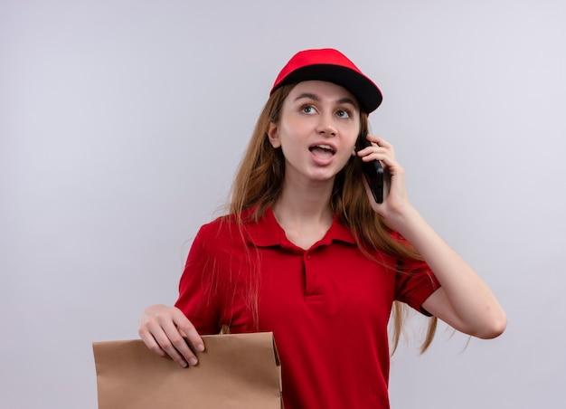 Jong leveringsmeisje in rode uniforme papieren zak houden en praten over de telefoon op geïsoleerde witte muur