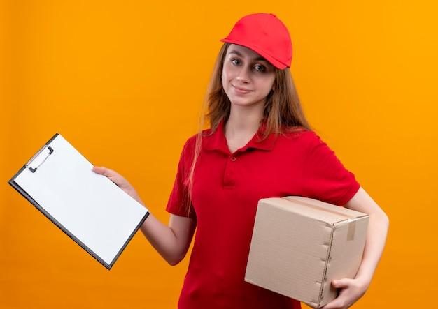 Jong leveringsmeisje in rood eenvormig holdingsdoos en klembord op geïsoleerde oranje muur