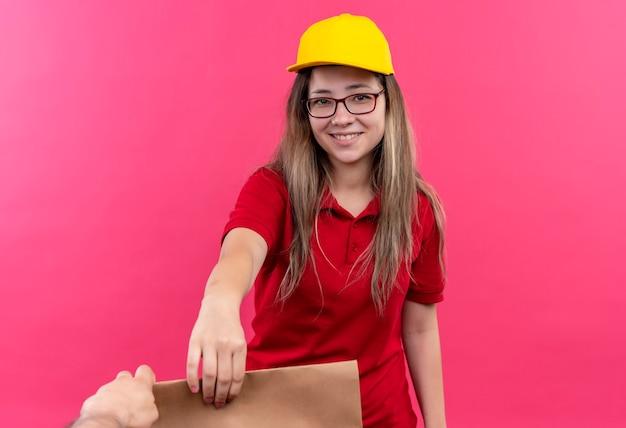 Jong leveringsmeisje in rood poloshirt en geel capgiving-document pakket aan een klant vriendelijk glimlachen