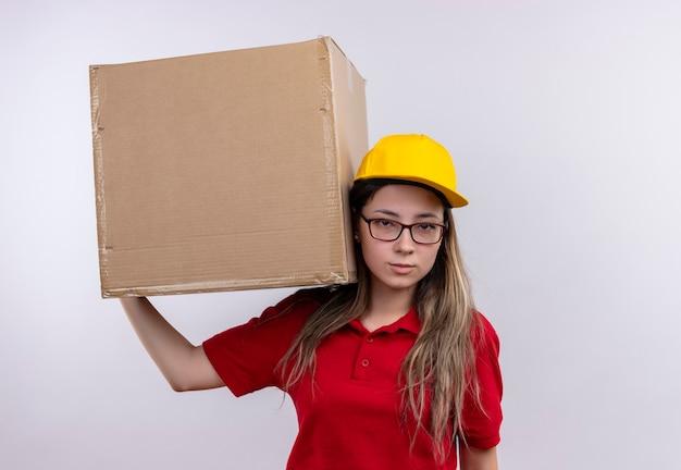 Jong leveringsmeisje in rood poloshirt en geel de doospakket van de glbholding die camera met ernstige zekere uitdrukkingen op gezicht bekijken