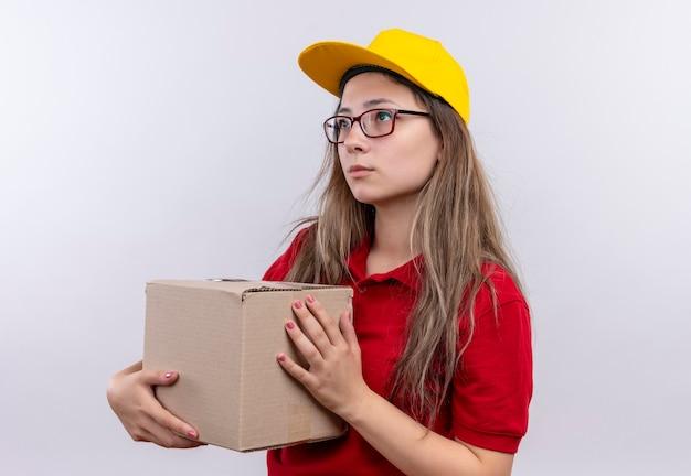 Jong leveringsmeisje in rood poloshirt en geel de doospakket van de glbholding die opzij met droevige uitdrukking op gezicht kijken