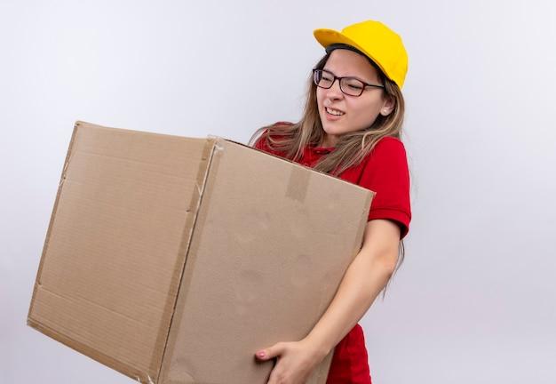 Jong leveringsmeisje in rood poloshirt en geel de doospakket van de glbholding ziet er onwel uit die aan het gewicht van de doos lijdt