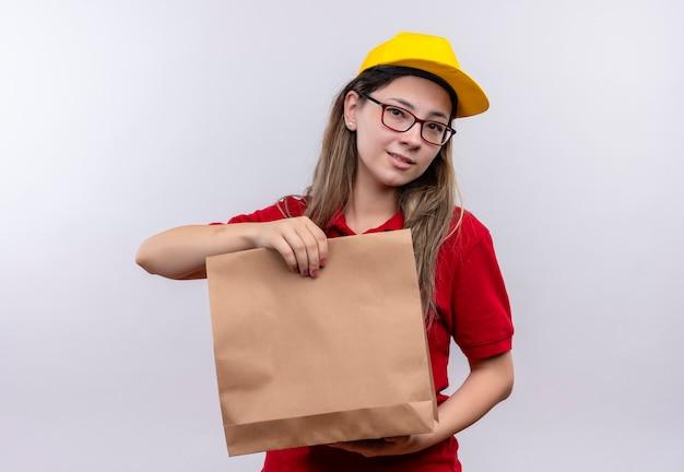 Jong leveringsmeisje in rood poloshirt en geel glb die document pakket houden die camera met ernstige zekere uitdrukking bekijken