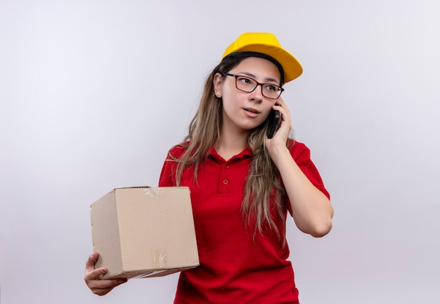 Jong leveringsmeisje in rood poloshirt en geel glb-doospakket houden tijdens het gesprek op mobiele telefoon met ernstig gezicht