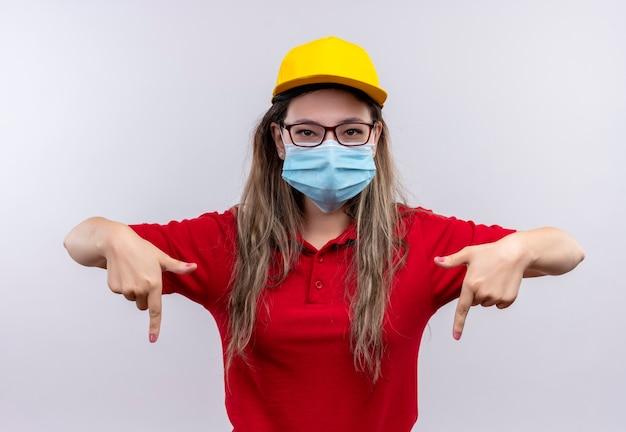 Jong leveringsmeisje in rood poloshirt en gele pet die beschermend gezichtsmasker dragen dat met wijsvingers naar beneden richt