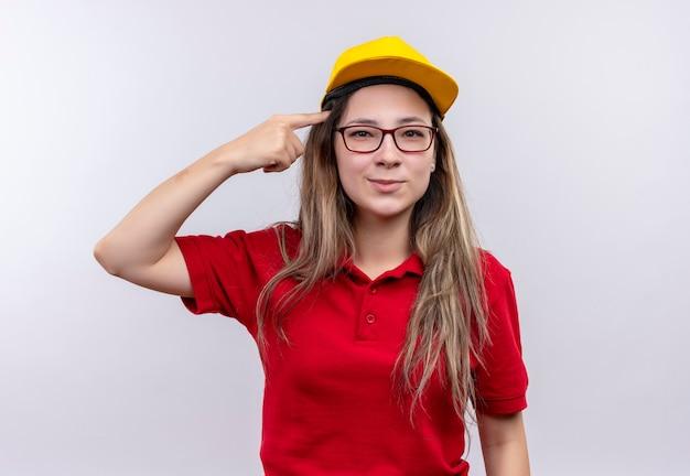 Jong leveringsmeisje in rood poloshirt en gele pet die haar tempel met wijsvinger richten die op een taak concentarting