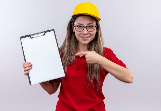 Jong leveringsmeisje in rood poloshirt en gele pet die klembord met blanco pagina's tonen die met vinger ernaar wijzen