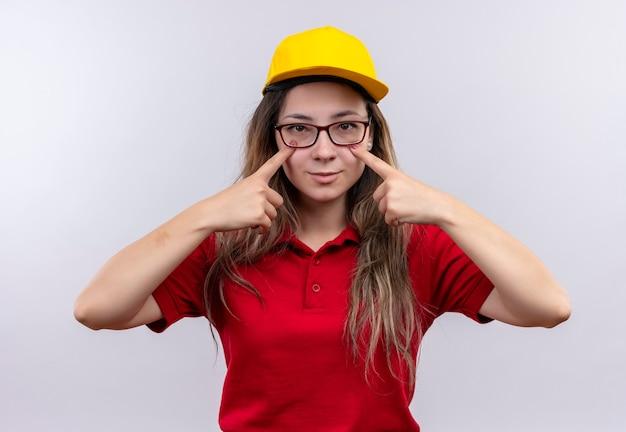 Jong leveringsmeisje in rood poloshirt en gele pet die met wijsvingers richten aan haar ogen het glimlachen