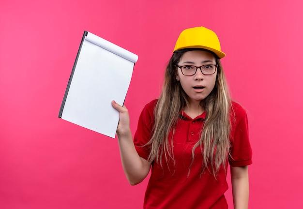 Jong leveringsmeisje in rood poloshirt en het gele klembord van de glbholding met blanco pagina's die teleurgesteld kijken