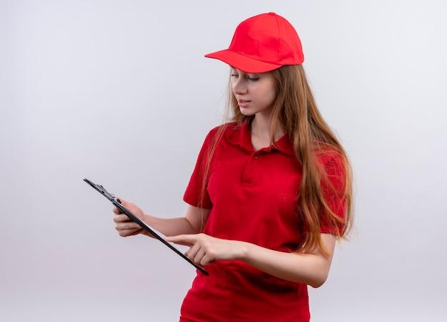 Jong leveringsmeisje in rood uniform die en vinger op klembord houden en bekijken op geïsoleerde witte muur