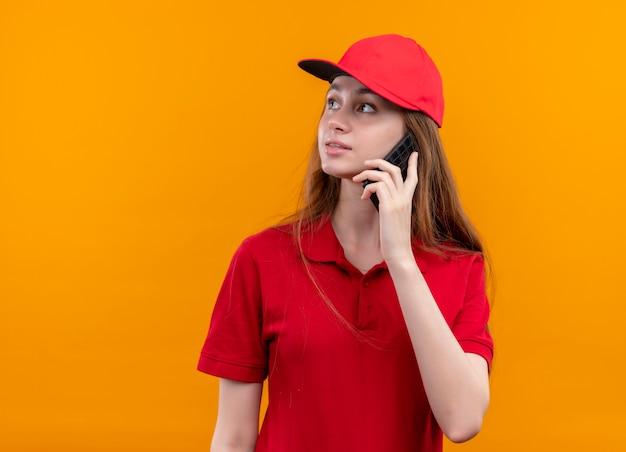 Jong leveringsmeisje in rood uniform die op telefoon spreken die naar linkerkant op geïsoleerde oranje muur met exemplaarruimte kijken
