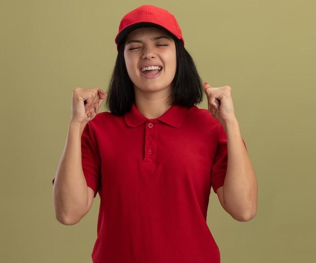 Jong leveringsmeisje in rood uniform en glb blij en opgewonden gebalde vuisten die zich over lichte muur bevinden
