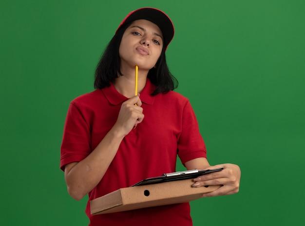 Jong leveringsmeisje in rood uniform en glb die pizzadoos en klembord met potlood in verwarring brengen status over groene muur