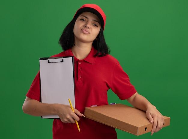 Jong leveringsmeisje in rood uniform en glb die pizzadoos en klembord met potlood met zekere uitdrukking houden die zich over groene muur bevinden