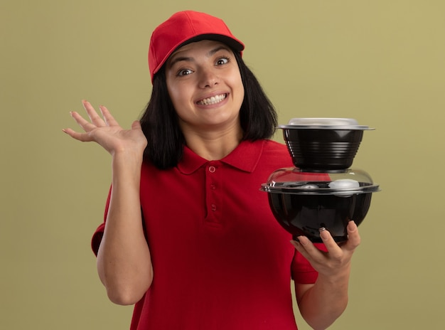 Jong leveringsmeisje in rood uniform en glb die voedselpakketten glimlachen die met hand golven die zich over lichte muur bevinden