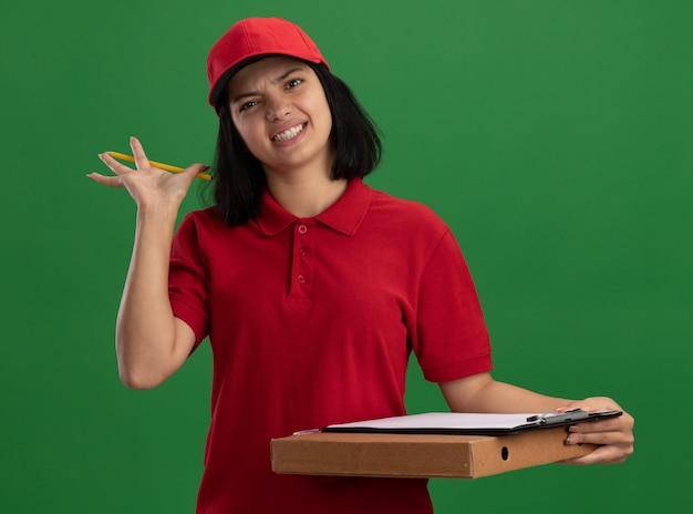 Jong leveringsmeisje in rood uniform en pet die pizzadoos en klembord met potlood met geïrriteerde uitdrukking houden die zich over groene muur bevinden