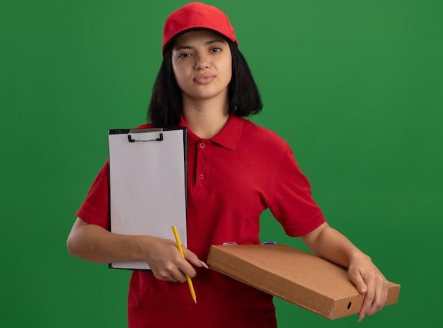Jong leveringsmeisje in rood uniform en pet die pizzadoos en klembord met potlood met zekere glimlach op gezicht houden die zich over groene muur bevinden
