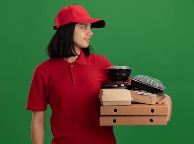 Jong leveringsmeisje in rood uniform en pet die pizzadozen en voedselpakketten houden die opzij met glimlach op gezicht over groene muur kijken