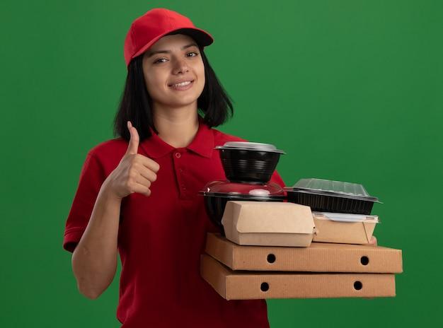 Jong leveringsmeisje in rood uniform en pet die pizzadozen en voedselpakketten met glimlach op gezicht houden die duimen tonen die zich over groene muur bevinden