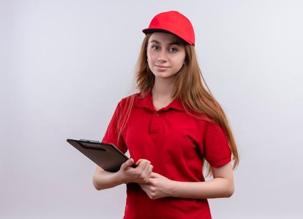 Jong leveringsmeisje in rood uniform holdingsklembord en op geïsoleerde witte muur