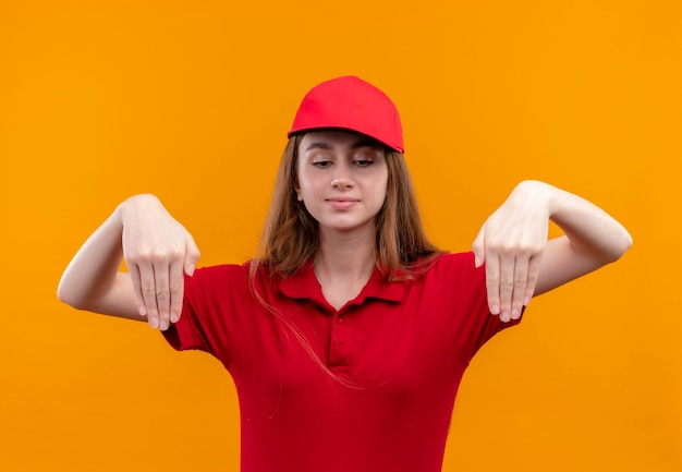 Jong leveringsmeisje in rood uniform wijzend met handen naar beneden en neerkijkend op geïsoleerde oranje muur