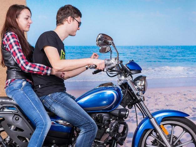 Jong lief stel in trendy outfits op een blauwe motor met rustige strandachtergrond